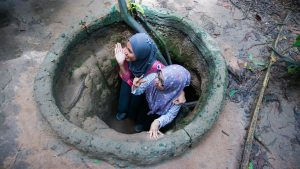 Two girls sneaking in Cu Chi Tunnels, Saigon, Vietnam, offered in a tour with Asia Vacation Group